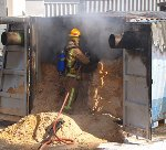 A firefighter douses down after the container blast. Picture: SunLive